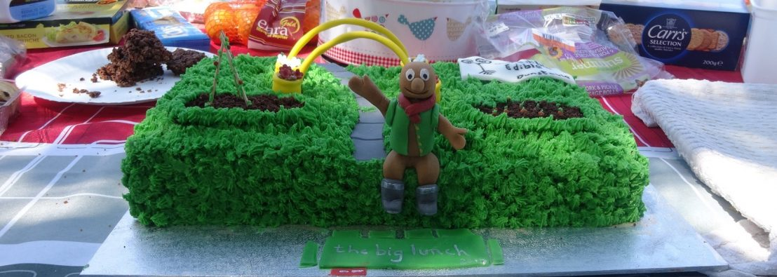 Close up of a cake on a table of party food which is outside - the cake is decorated to look like a garden and has TV character Morph in wellies waving