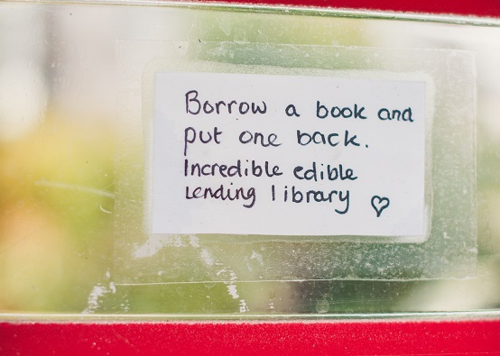 Hand written label stuck on a window saying 'borrow a book and put one back. Incredible Edible lending library'