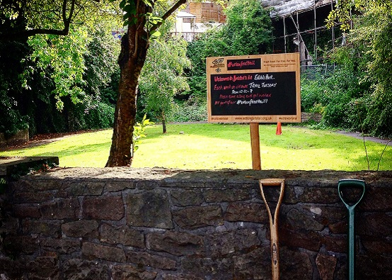 View of a green park with an Incredible Edible Bristol sign