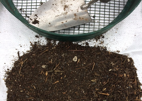 Pile of fresh compost next to a sieve and trowel, with a spider next to the compost