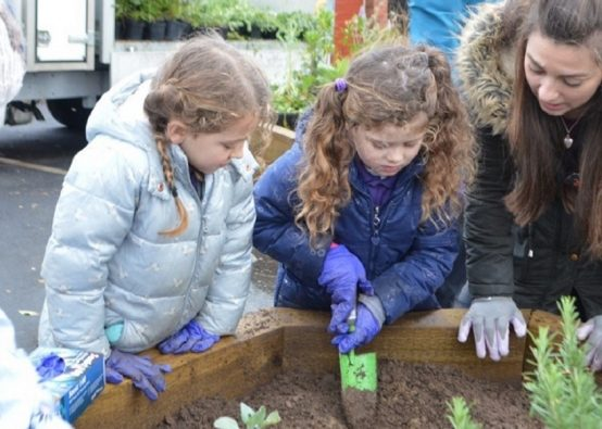 Three girls and a teacher, wrapped up warm and wearing gardening gloves are planting up a new raised bed