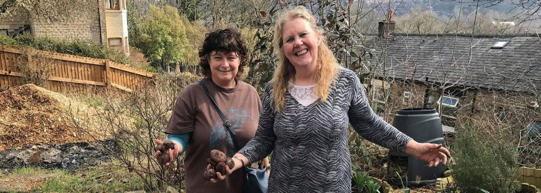 Two members of Incredible Edible Mossley on their growing site