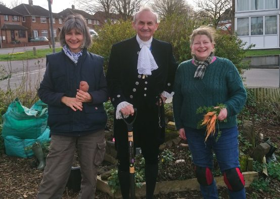 High Sheriff, Julian Polehill, flanked by two members of Incredible Edible Dunstable, next to a growing bed in a residential area