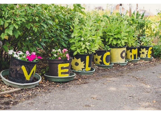 Row of buckets with letters on each spelling welcome - each bucket has plants growing in them and they're in a residential area